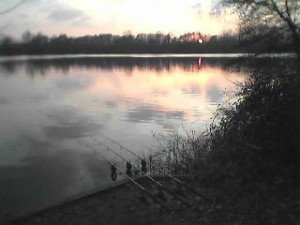 A view across a winter gravel pit at sunset