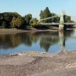 The Thames viewed from Hammersmith, looking across to Castelnau on a sunny autumn day with the tide out